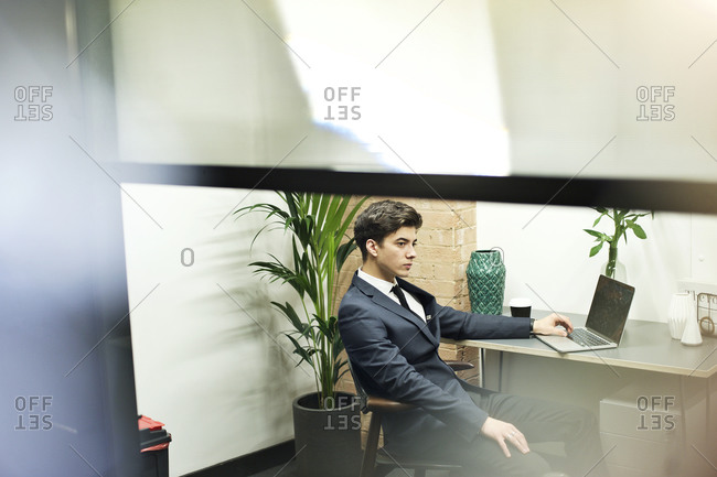 Young business man daydreaming at his desk