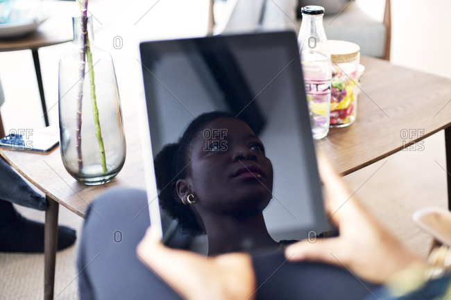 Reflection of a young business woman in a tablet