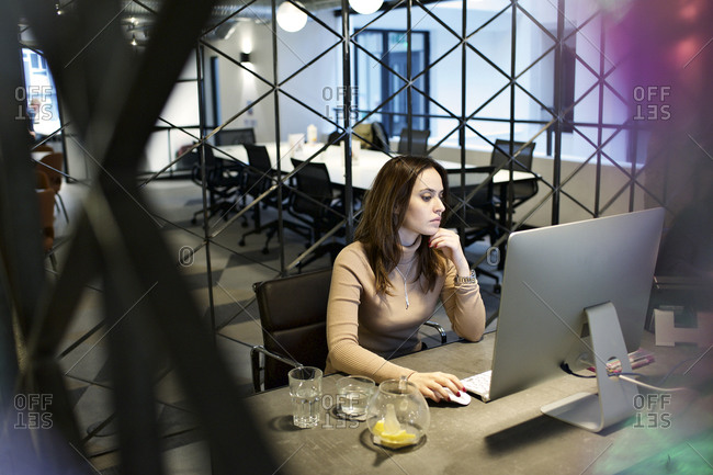Young woman working in an office with a geometric divider