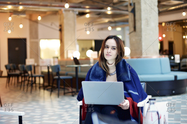 Young business woman in a lobby working on a laptop