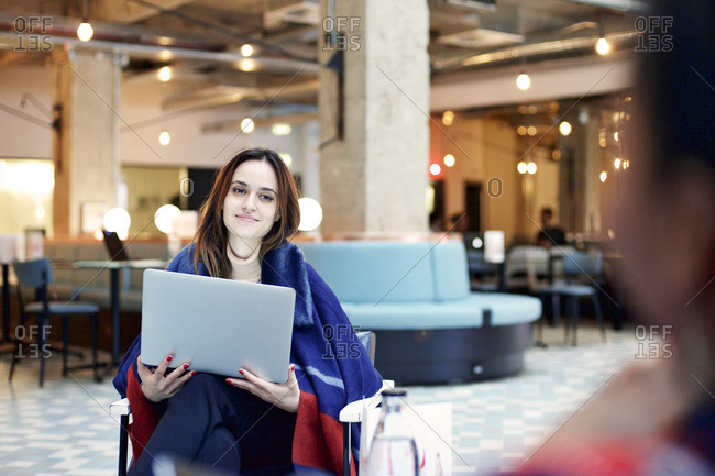 Young woman working in a lobby and smiling