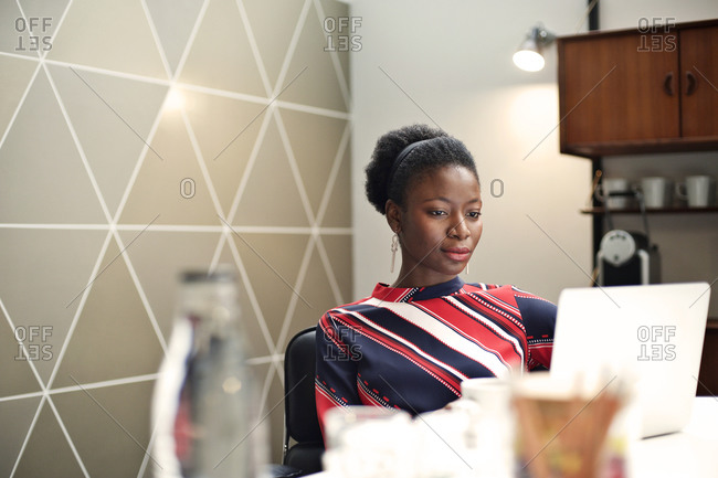 Young woman sitting in a break room working on a laptop