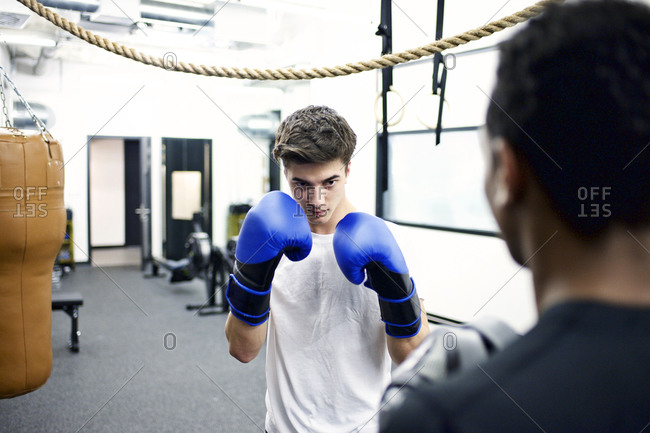 Young men practicing boxing in their company's gym
