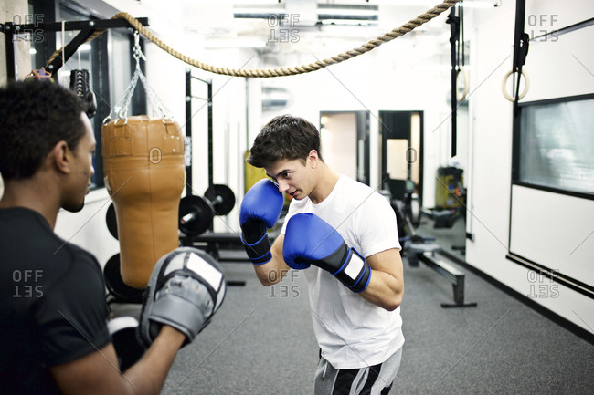 Young men boxing in their company's gym