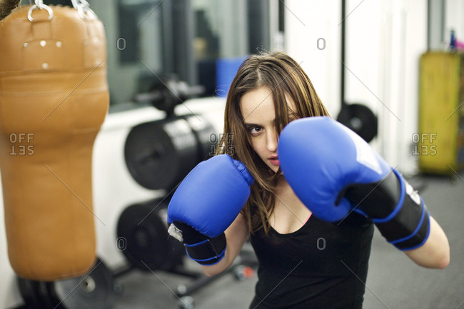 Young woman practicing boxing in her company gym
