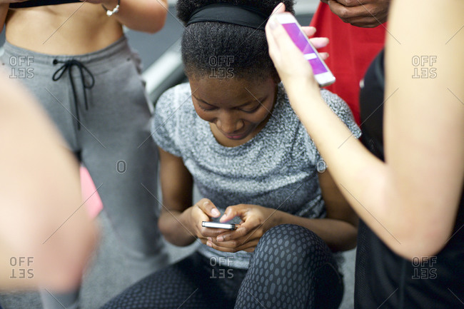Young women standing in a group texting
