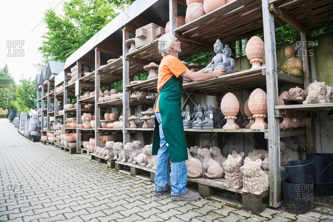 Male gardener arranging ceramic sculpture in shelf, Augsburg, Bavaria, Germany