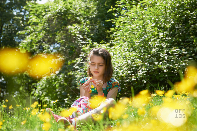 Girl making floral crown in park, Munich, Bavaria, Germany