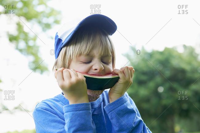 Boy enjoying slice of watermelon at picnic, Munich, Bavaria, Germany