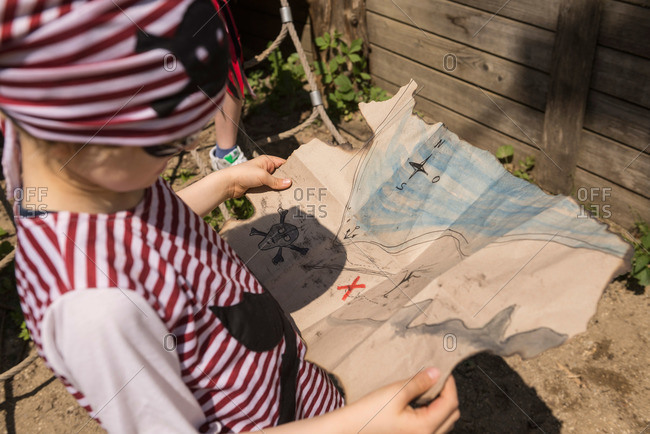 Close-up of a boy examining a treasure map in a adventure playground, Bavaria, Germany
