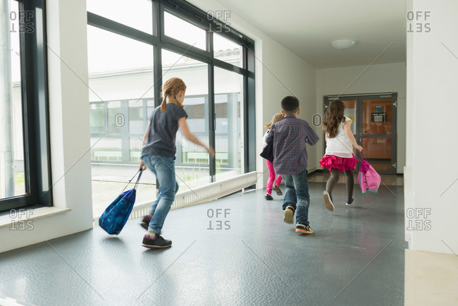 Children running with sports bags in corridor of sports hall, Munich, Bavaria, Germany