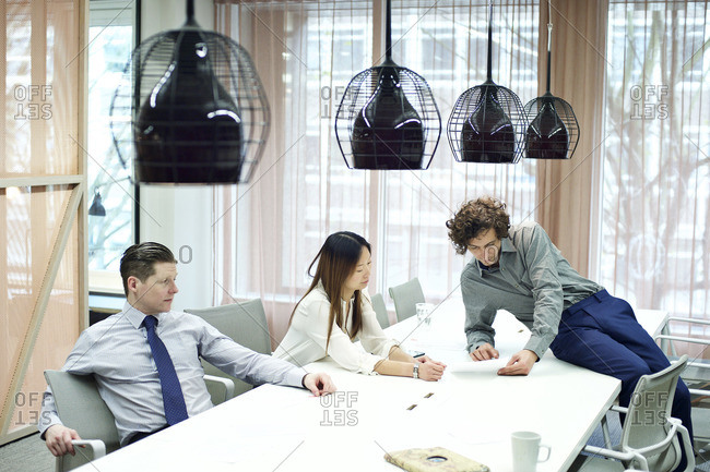 Coworkers looking at paperwork in a conference room