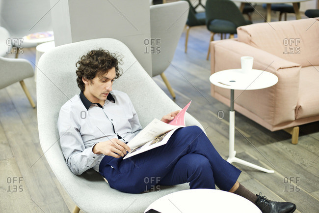Man reading a magazine in an office lounge
