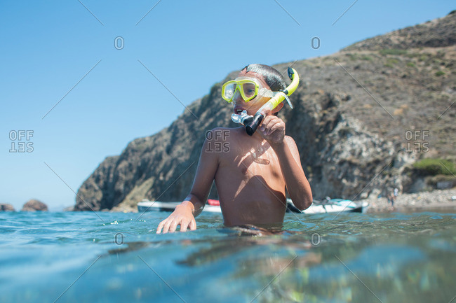 Young boy standing in shallow water with snorkel mask on