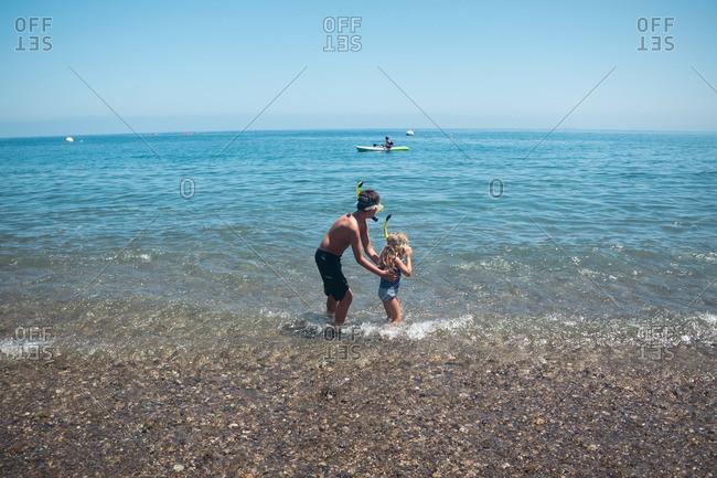 Children standing in shallow water wearing snorkel masks