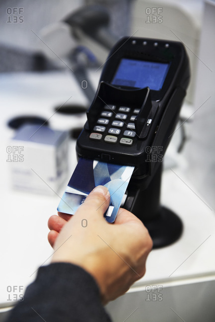 Hand putting bank card into card reader