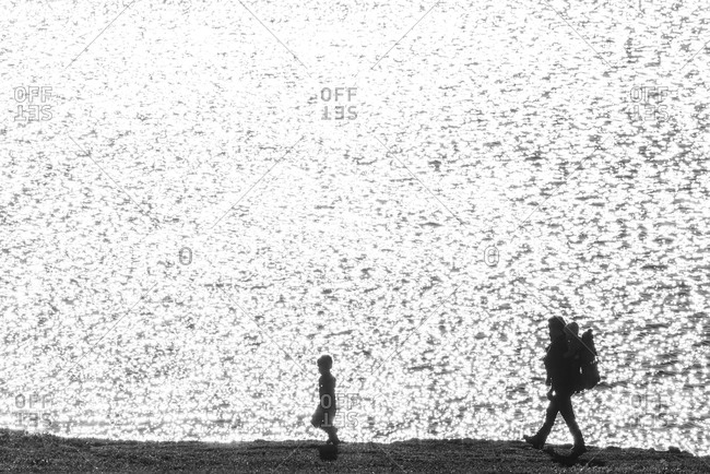 Silhouettes of father with children at sea