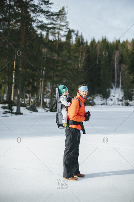 Man walking on ice lake with baby in baby carrier