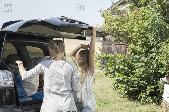 Two girls standing by car trunk
