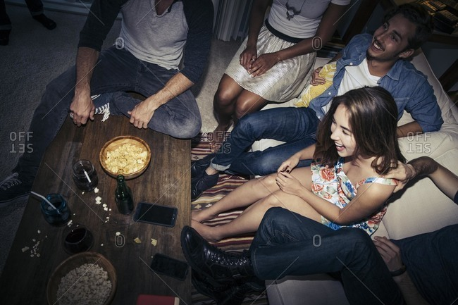 Group of friends sitting together with beverages and popcorn
