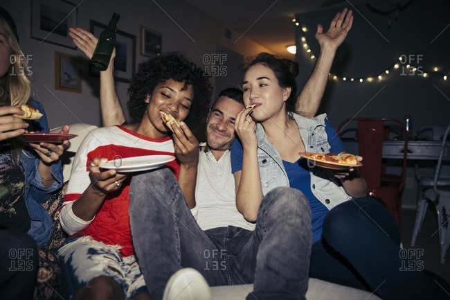 Friends eating pizza on sofa together