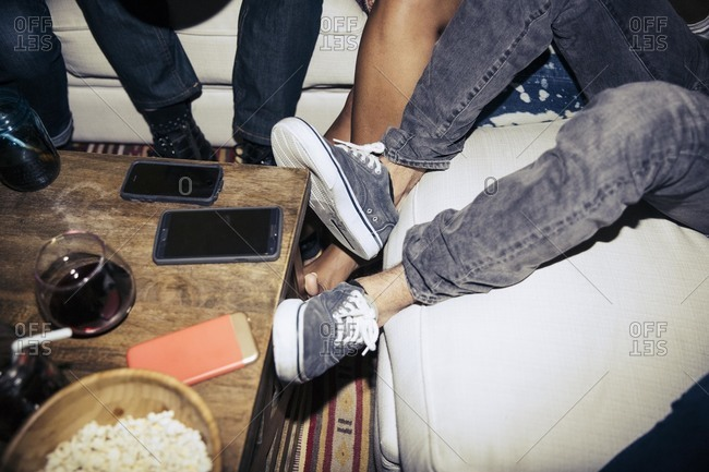 People's feet surrounding three smartphones on table