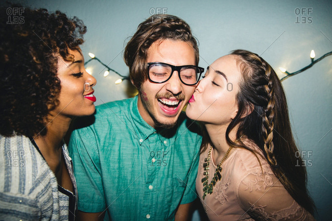 Women kissing man on cheeks at party