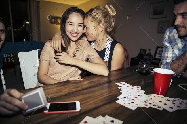 Affectionate women sitting at table with friends