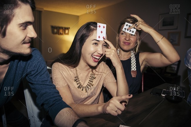 Friends playing a card game at party