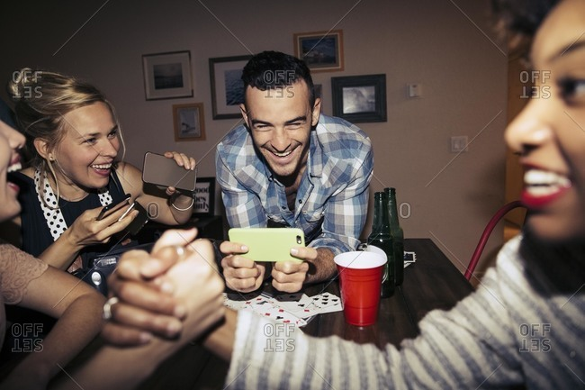 Man taking a picture of friends arm wrestling