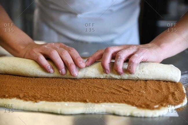 Baker's hands rolling up dough with cinnamon mixture