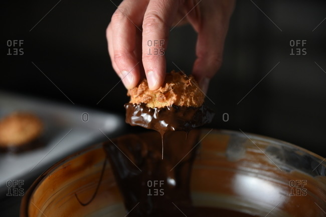 Close-up of baker's hand dipping coconut macaroon into melted chocolate