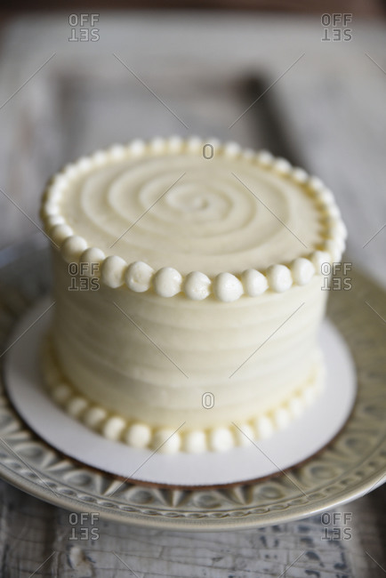 Small frosted cake with decorated edges on plate