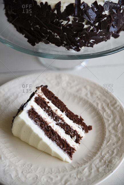 Slice of triple layer chocolate cake with white icing below whole cake