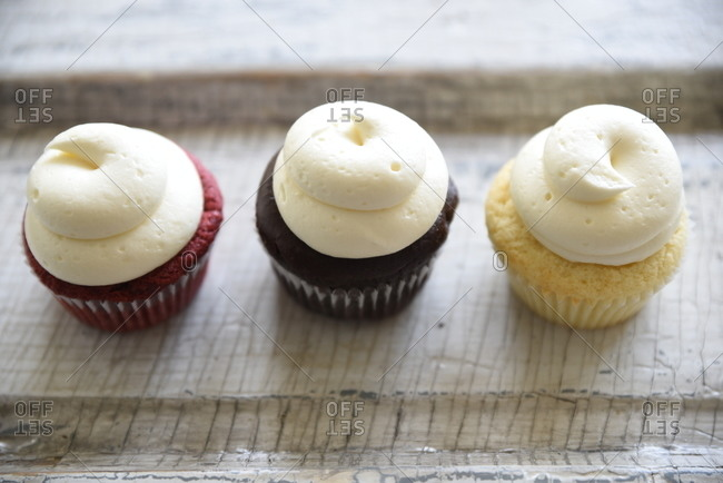 Elevated view of three different colored cupcakes with frosting