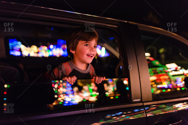 Boy looking at Christmas lights display out car window