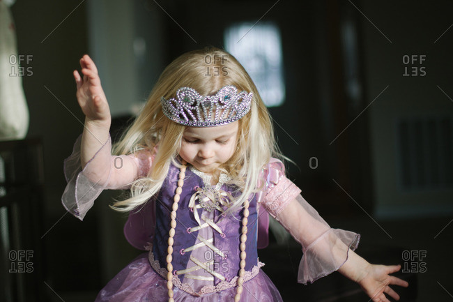 Young girl playing in princess dress and crown