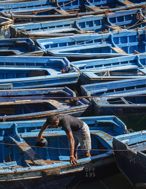 Man scooping water out of his fishing boat, Essaouira, Morocco