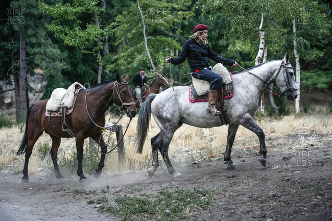 Patagonia, Argentina - February 24, 2012: Gaucho woman entering an estancia with two horses, Patagonia, Argentina