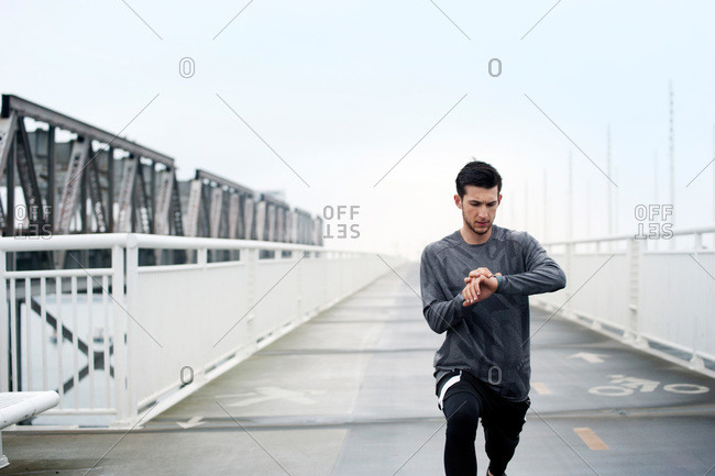 Man setting his fitness monitor while stretching before workout