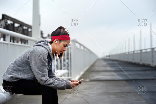 Woman using her smartphone before workout on bridge