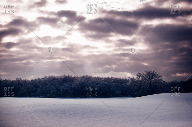 Sun rays coming through cloud over snowy field