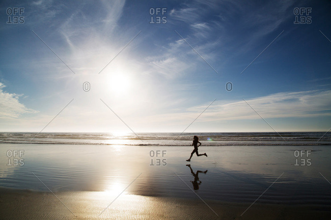 Reflection of woman running on beach