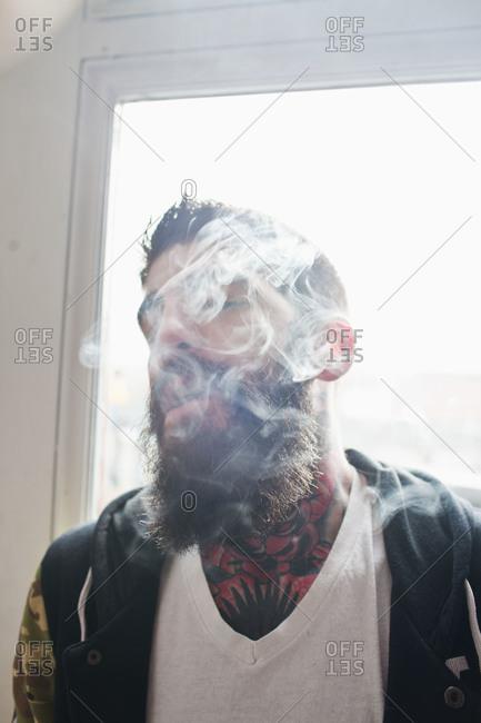 Young man with tattoos smoking