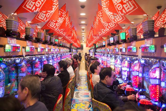 Tokyo, Japan - November 27, 2015: Rows of men playing Pachinko games in Tokyo