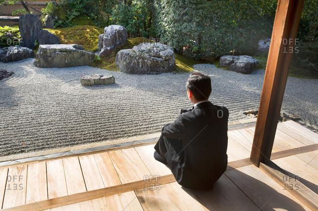 Man sitting in front of zen garden at Tofukuji Temple in Kyoto, Japan