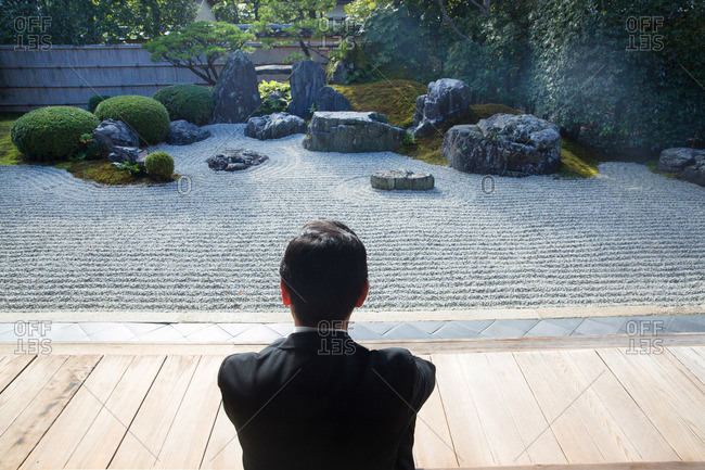 Back view of man contemplating zen garden at Tofukuji Temple in Kyoto, Japan
