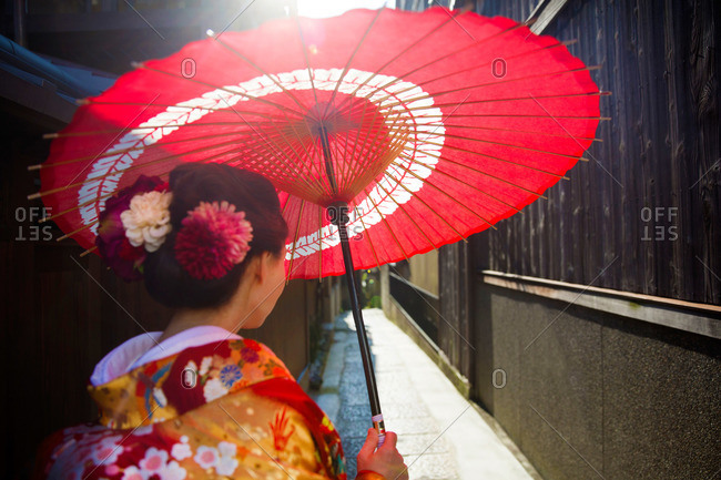 Woman in traditional clothing with an oil paper umbrella in an alleyway in Kyoto, Japan