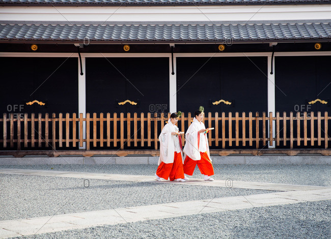 Kyoto, Japan - November 30, 2015: Two Shinto priestesses walking in a shrine in Kyoto, Japan