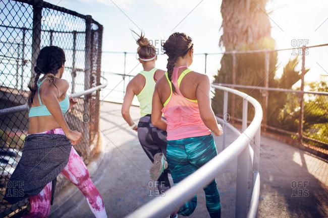 Women jogging on a pedestrian bridge